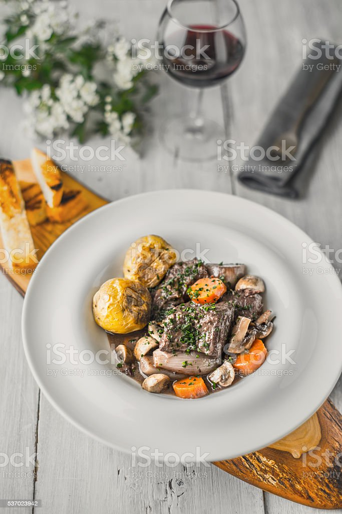 Beef bourguignon in a ceramic dish on a wooden stand Lizenzfreies stock-foto