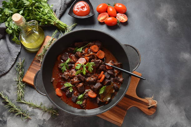 Beef Bourguignon in a pan Beef Bourguignon in a pan. Stew with red wine ,carrots, onions, garlic, a bouquet garni, and garnished with pearl onions, mushrooms and bacon. French cuisine- regional recipe from Burgundy beef bourguignon stock pictures, royalty-free photos & images