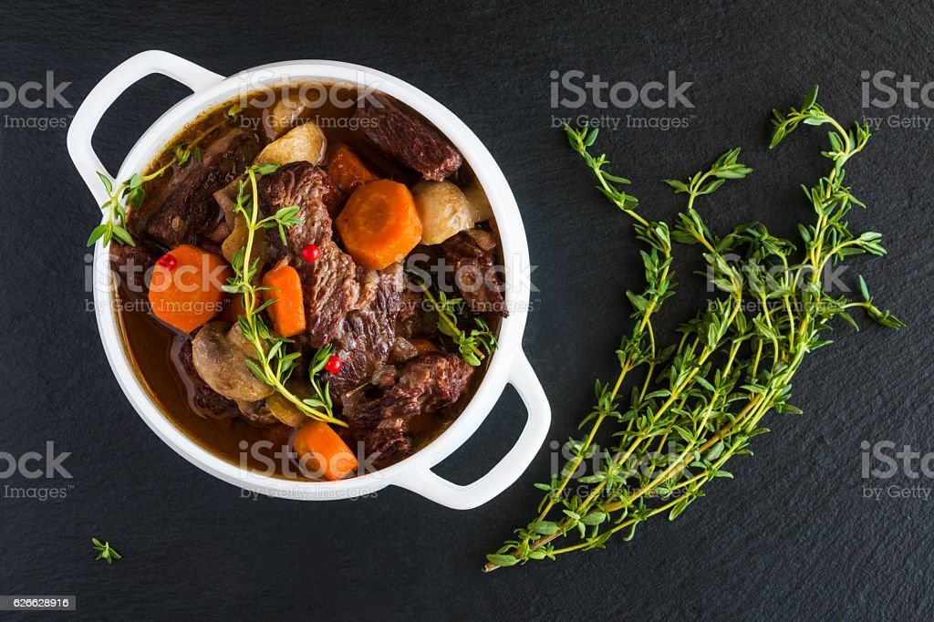 Beef Bourguignon in a white soup bowl on black stone Beef Bourguignon in a white soup bowl on black stone background, top view. Stew with carrots, onions, mushrooms, bacon, garlic and bouquet garni. The dish is served with fresh thyme. Bacon Stock Photo