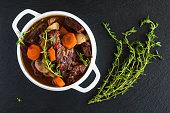 Beef Bourguignon in a white soup bowl on black stone