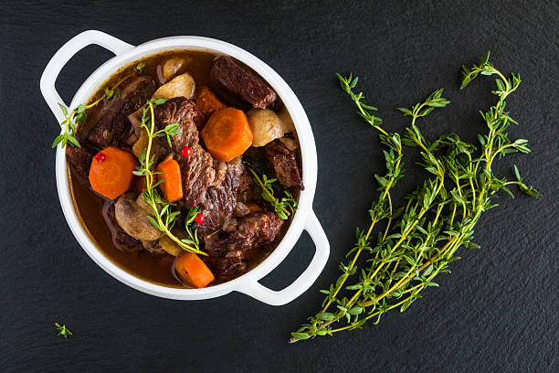 Beef Bourguignon in a white soup bowl on black stone Beef Bourguignon in a white soup bowl on black stone background, top view. Stew with carrots, onions, mushrooms, bacon, garlic and bouquet garni. The dish is served with fresh thyme. ragout stock pictures, royalty-free photos & images