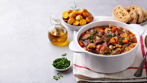 Beef bourguignon stew with vegetables. Grey background. Copy space. stock photo