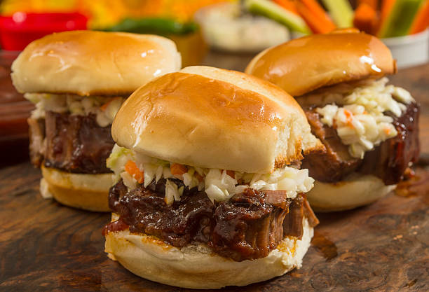 beef brisket sliders smothered in  sauce and topped with slaw stock photo