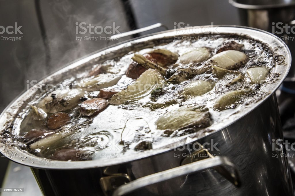 Beef broth boiling in a metal pot stock photo