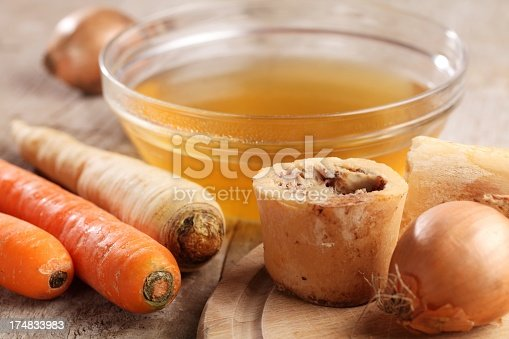 Bowl with beef broth, boiled bones and fresh vegetables.
