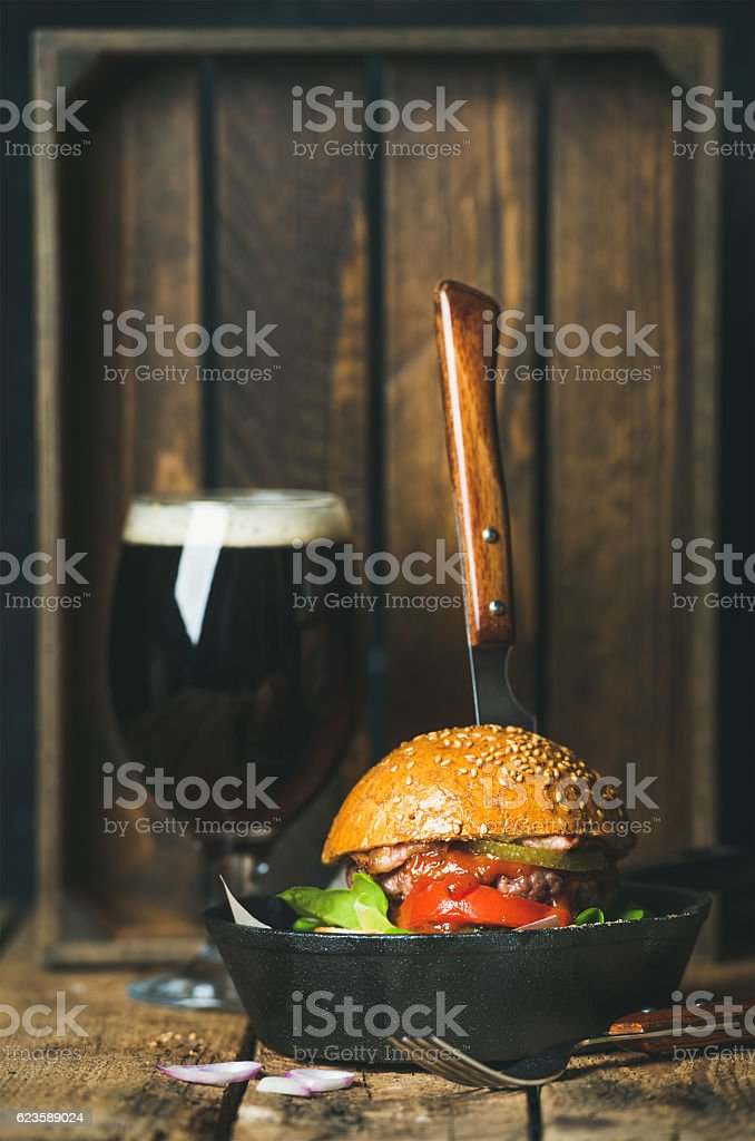 Beef burger with crispy bacon in pan and dark beer stock photo
