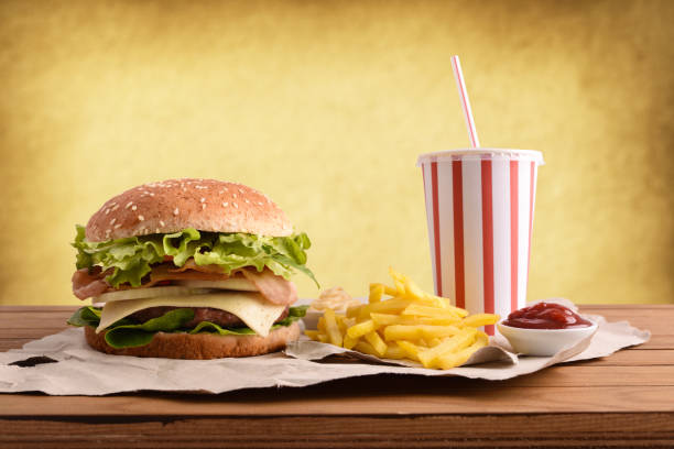 beef burger with soda chips and souces on table golden - fast food restaurant stock pictures, royalty-free photos & images