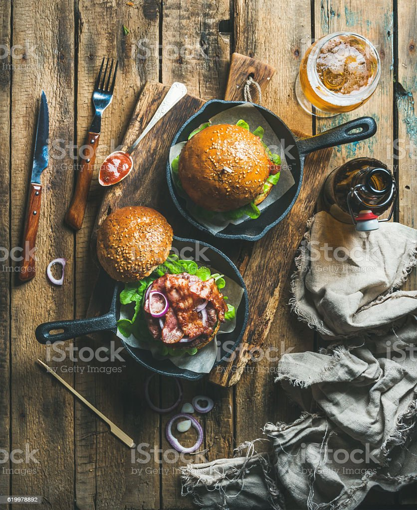 Beef burgers in cast iron pans and glass of beer stock photo