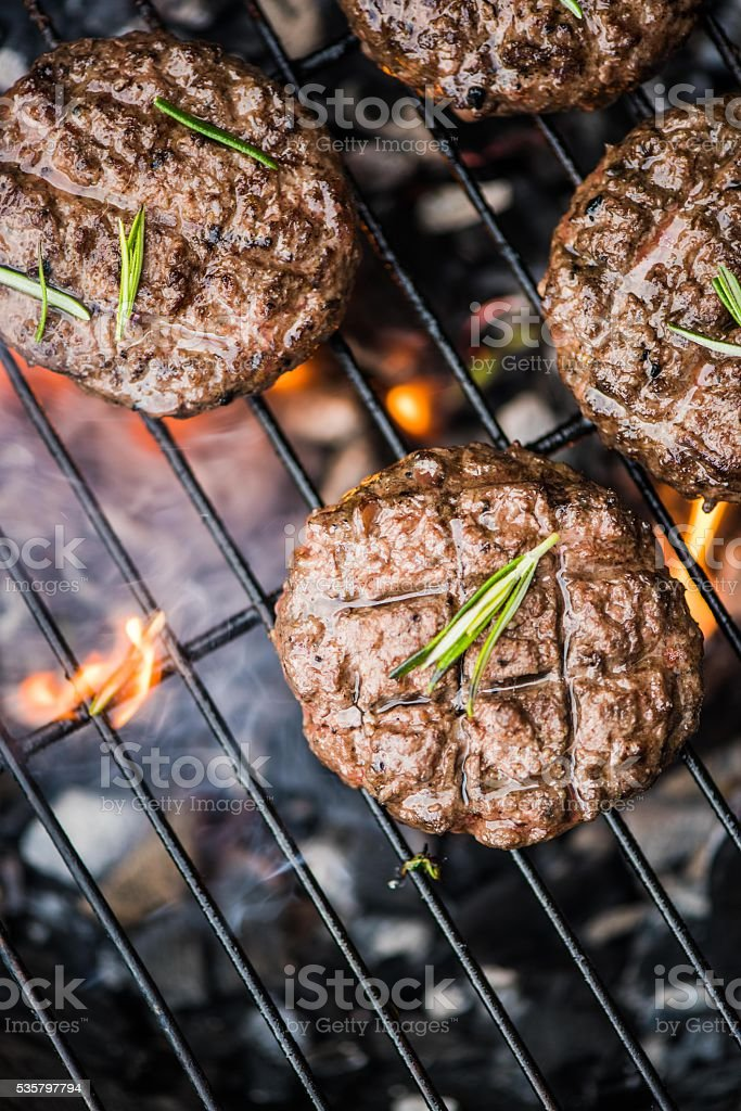 beef burgers on grill with flames​​​ foto