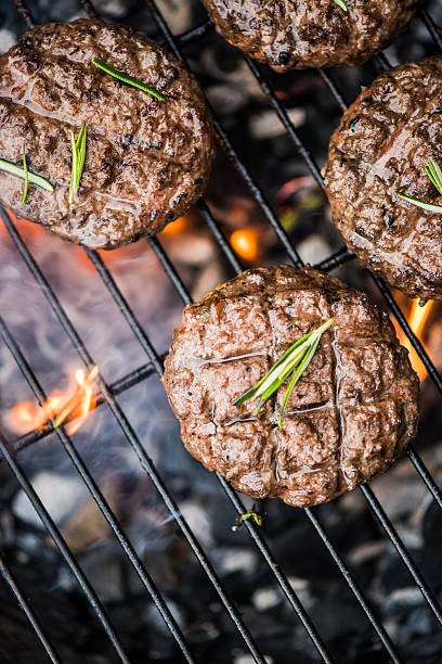 beef burgers on grill with flames stock photo