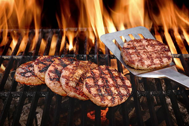 Beef Burgers On The Hot Flaming BBQ Charcoal Grill stock photo