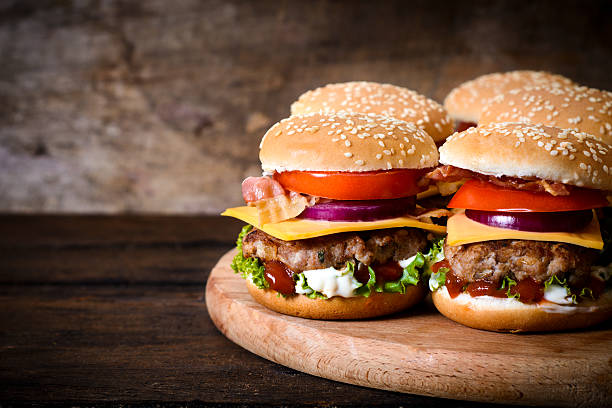 Beef burgers Beef burgers on the wooden background with blank space on left ide slider burger stock pictures, royalty-free photos & images