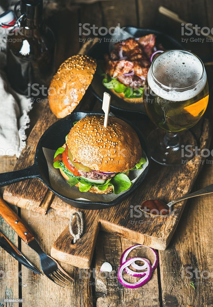Beef burgers with crispy bacon, fresh vegetables and wheat beer stock photo