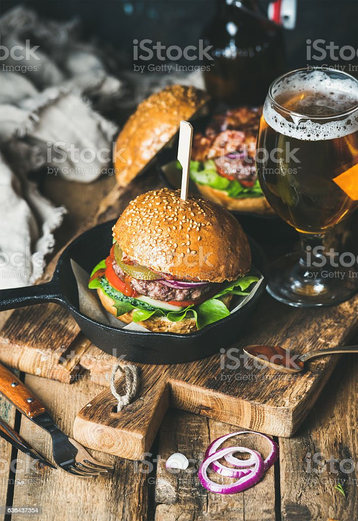 Beef burgers with crispy bacon, vegetables and glass of beer stock photo