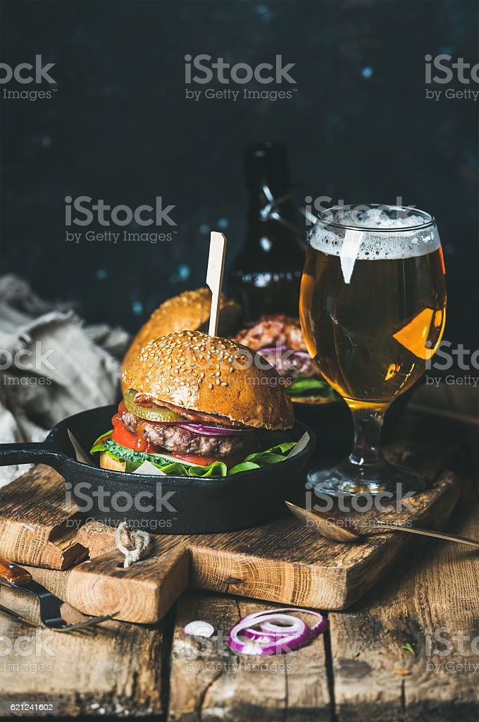 Beef burgers with crispy bacon, vegetables, glass of beer stock photo