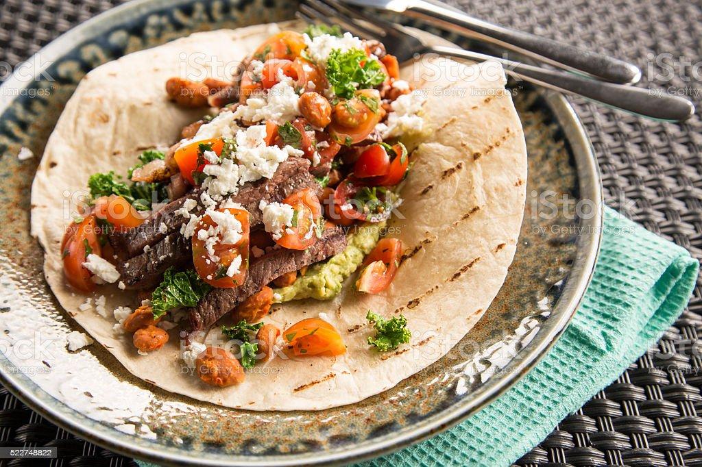 Beef Burrito with chilli lime greens & feta stock photo