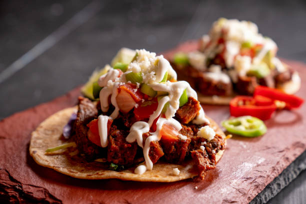 Beef Carne Asada Mexican Tijuana Style Street Food Tacos with Marinated Steak, Cilantro, Onion, Cotija Cheese and Sour Cream stock photo