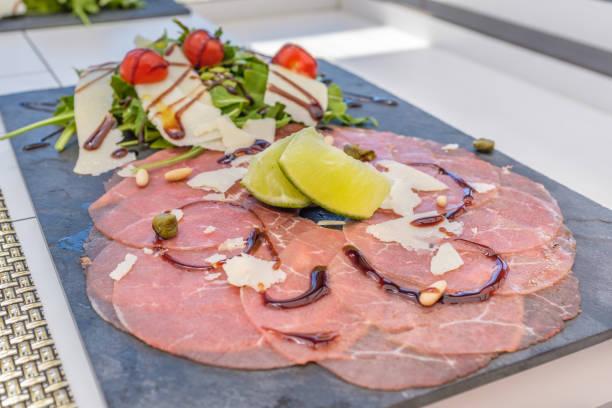 rindfleisch-carpaccio auf einem schiefer servierplatte - carpaccio salat stock-fotos und bilder