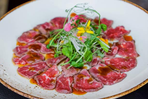 rindfleisch carpaccio mit blattgemüse - carpaccio salat stock-fotos und bilder