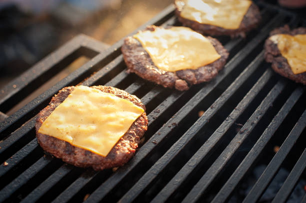 beef cutlets with cheese on the grill. street food. - cheeseburger стоковые фото и изображения