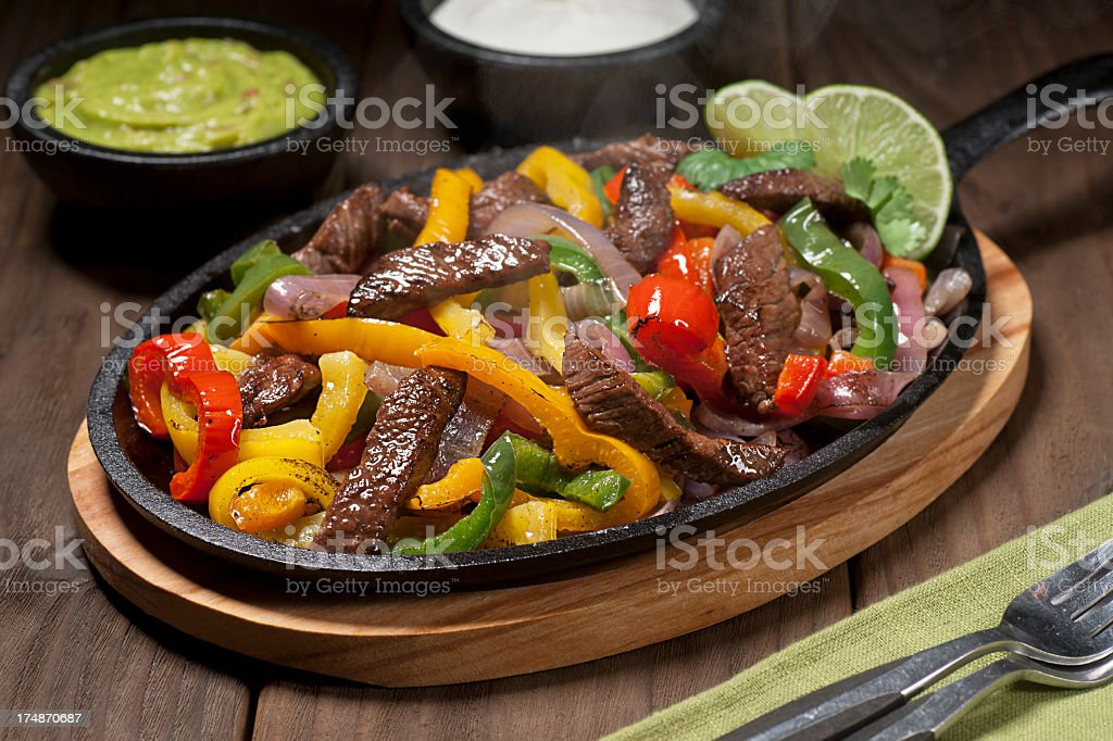 Beef fajitas in a skillet on a wooden table stock photo