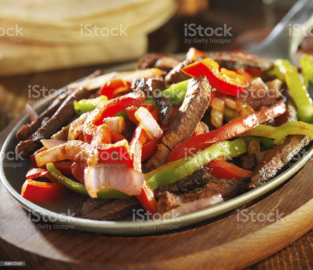 beef fajitas with green and red peppers in iron skillet stock photo