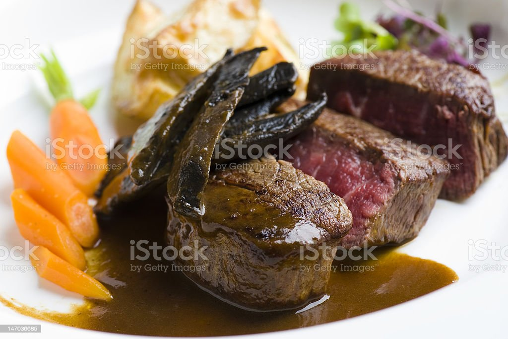 beef fillet served with mushroom, carrot and potato wedges royalty-free stock photo