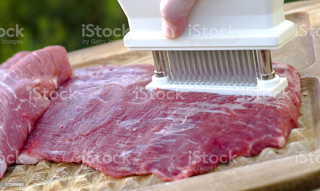 Beef Flank Steak being Tenderized stock photo