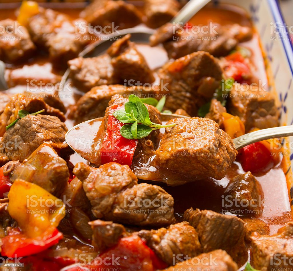 Beef goulash with vegetables and spoon, close up stock photo