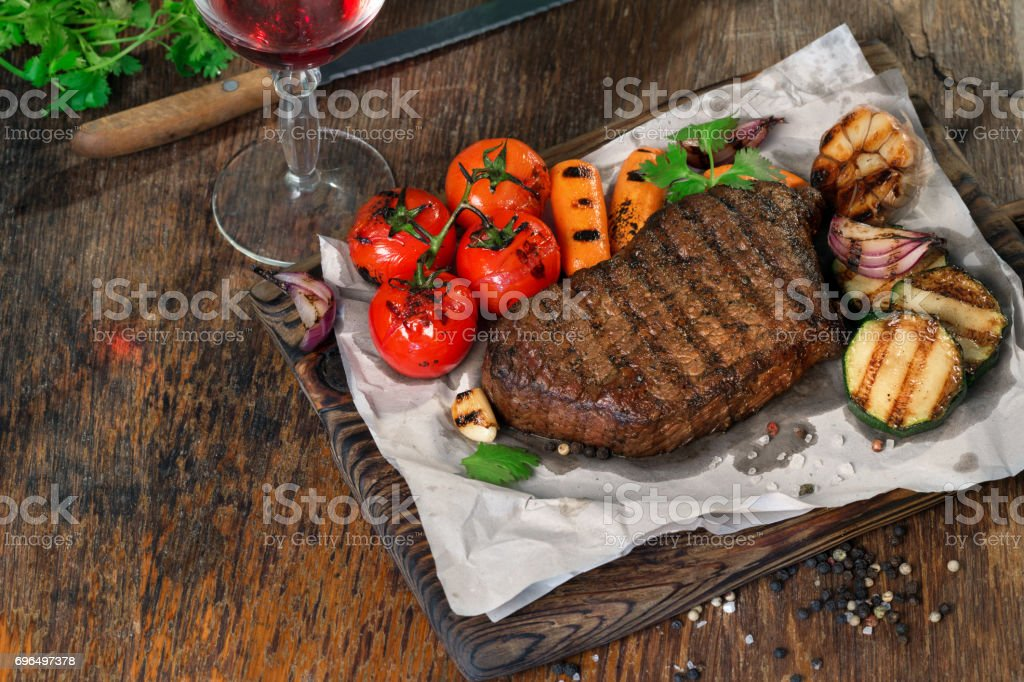 Beef grilled steak with set of grilled vegetables and glass of red wine on wooden table with copy space stock photo