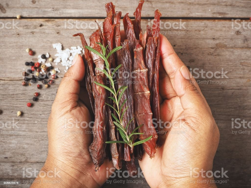 Beef jerky on hands stock photo