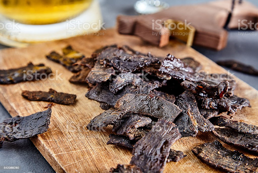Beef jerky on wood board and beer stock photo