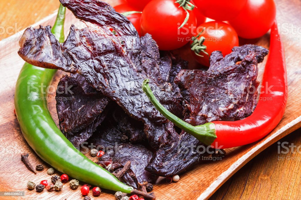 Beef jerky with vegetables and spices on a wooden tray stock photo
