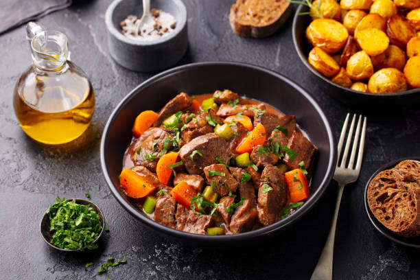 Beef meat and vegetables stew in black bowl with roasted baby potatoes. Dark background. stock photo