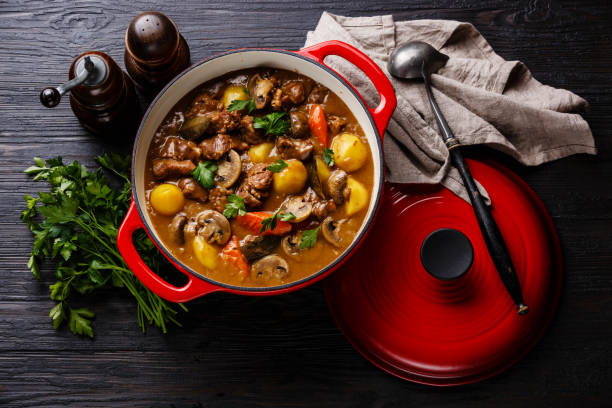 Beef meat stew with potatoes, carrots and spices Beef meat stewed with potatoes, carrots and spices in cast iron pan on burned black wooden background goulash stock pictures, royalty-free photos & images