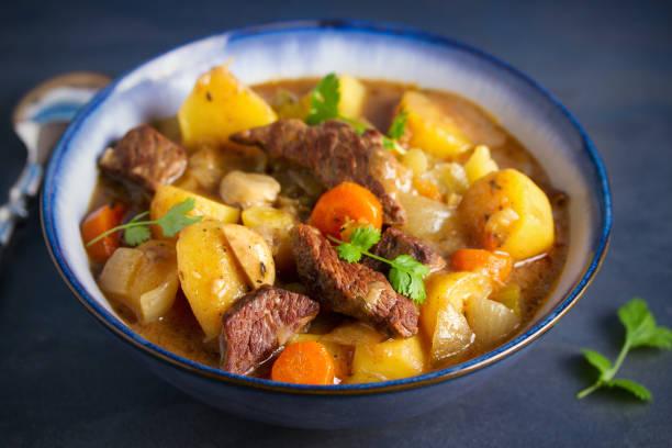 Carne de res guisada con patatas, zanahorias y especias en tazón sobre fondo gris oscuro - foto de stock
