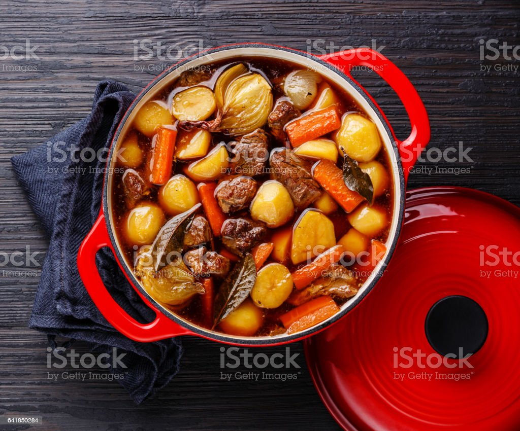 Beef meat stewed with potatoes in cast iron pot stock photo