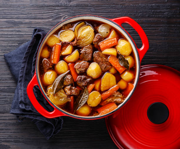 Beef meat stewed with potatoes in cast iron pot Beef meat stewed with potatoes, carrots and spices in cast iron pot on burned black wooden background goulash stock pictures, royalty-free photos & images