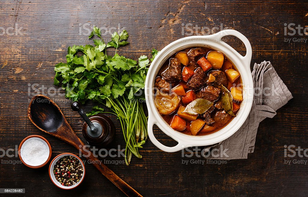 Beef meat stewed with potatoes in pot Beef meat stewed with potatoes, carrots and spices in ceramic pot Beef Stock Photo