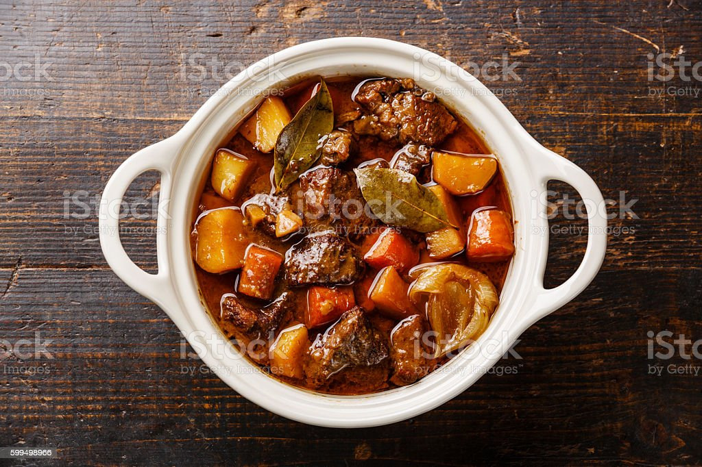 Beef meat stewed with potatoes Beef meat stewed with potatoes, carrots and spices in ceramic pot on wooden background Bay Leaf Stock Photo