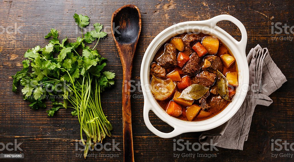 Beef meat stewed with potatoes Beef meat stewed with potatoes, carrots and spices in ceramic pot on wooden background Beef Stock Photo