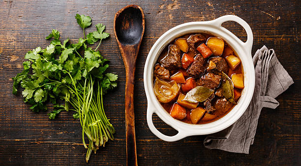 Beef meat stewed with potatoes Beef meat stewed with potatoes, carrots and spices in ceramic pot on wooden background goulash stock pictures, royalty-free photos & images