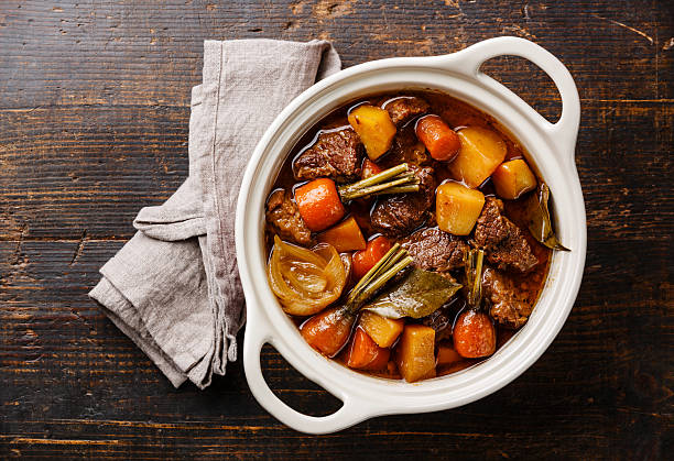 Beef meat stewed with potatoes Beef meat stewed with potatoes, carrots and spices in ceramic pot on wooden background beef bourguignon stock pictures, royalty-free photos & images