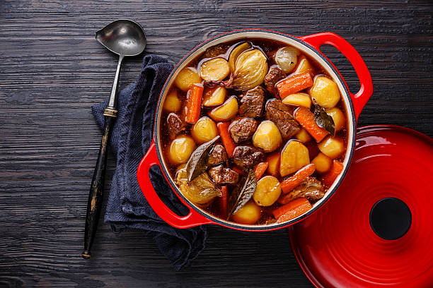 Beef meat stewed with potatoes Beef meat stewed with potatoes, carrots and spices in cast iron pot on burned black wooden background beef bourguignon stock pictures, royalty-free photos & images