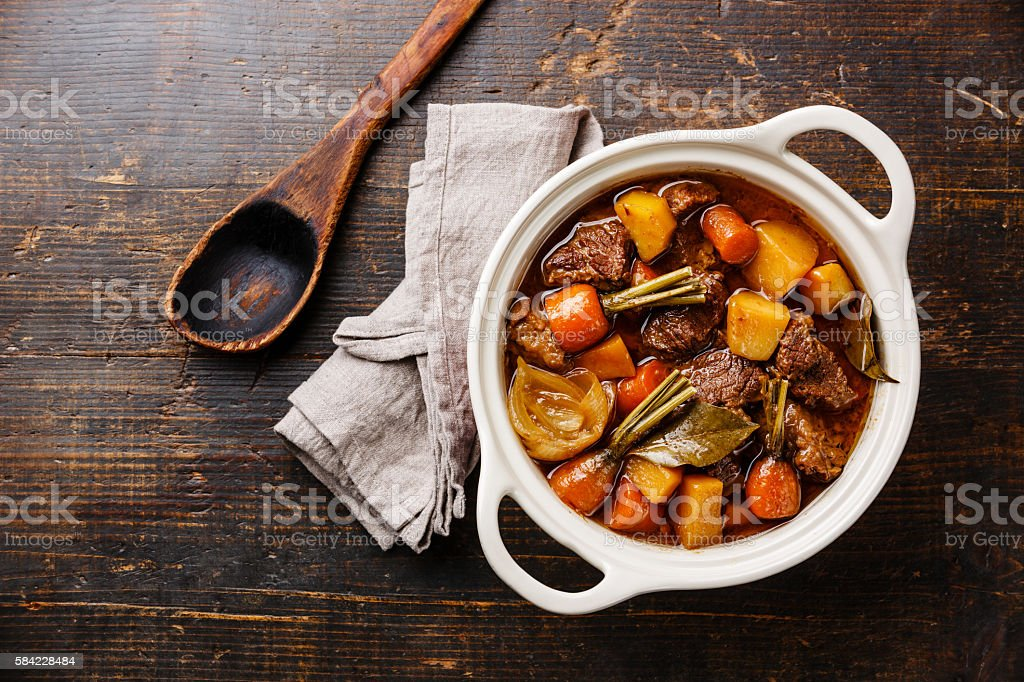 Beef meat stewed with vegetables Beef meat stewed with potatoes, carrots and spices in ceramic pot on wooden background Bay Leaf Stock Photo