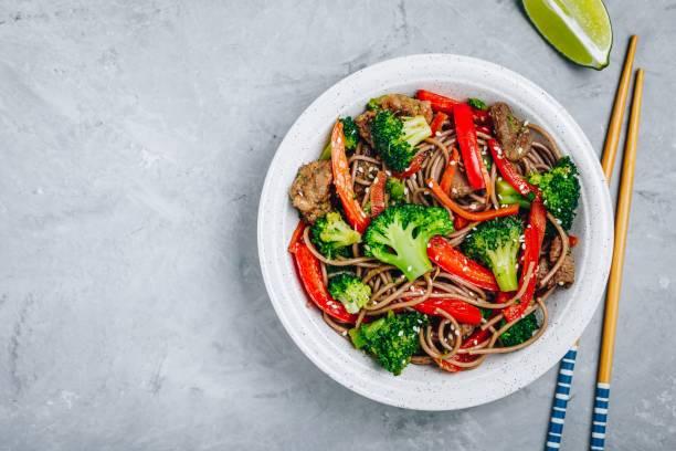 rundvlees noodle roerbak met broccoli, wortelen en rode paprika - sobanoedels stockfoto's en -beelden