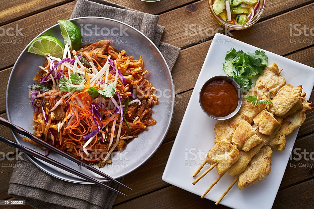 beef pad thai and chicken satay dinner viewed from above - foto de acervo