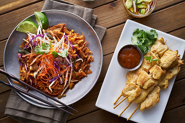 beef pad thai and chicken satay dinner viewed from above beef pad thai and chicken satay dinner viewed from above in flat lay composition asian food stock pictures, royalty-free photos & images