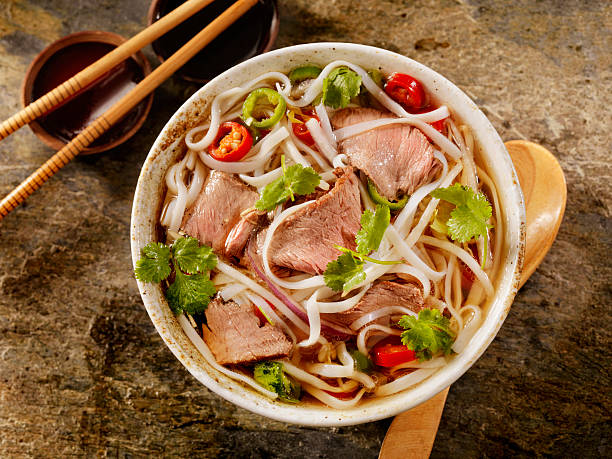 Beef Pho Grilled Beef and Rice noodle soup with Carrots, Onions, Peppers and Cilantro -Photographed on Hasselblad H1-22mb Camera rice noodles stock pictures, royalty-free photos & images