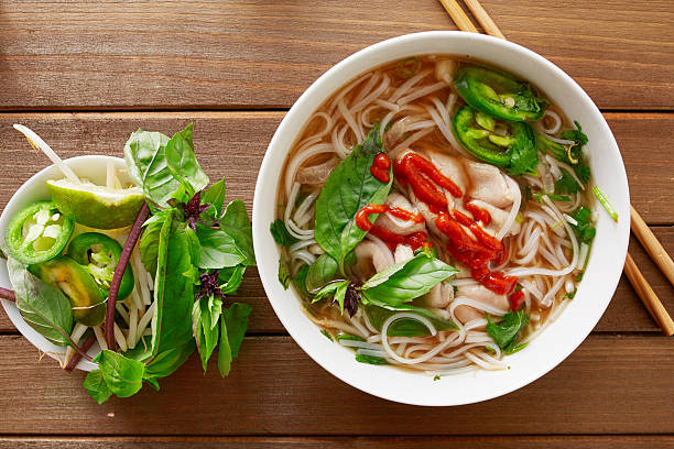 beef pho tai with sriracha sauce aerial view - pho soup stock photos and pictures